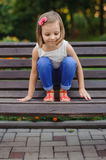 Little cute girl sits on bench Royalty Free Stock Image