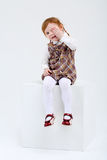 Little cute girl sits on big white cube Stock Photo