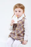 Little cute girl sits and drinks sweet juice Stock Images
