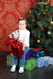 Little cute girl sits on gift on floor near Christmas tree Royalty Free Stock Images