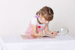 Little cute girl sits oat table, reads book Stock Photo