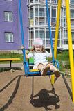 Little cute girl sits on swing Royalty Free Stock Photos