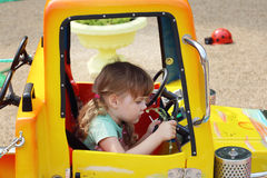 Little cute girl sits at wheel of big yellow toy car. At sunny day stock photos