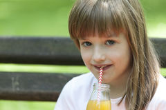 Little cute girl sitting on a bench and drinking her favorite ju Royalty Free Stock Image