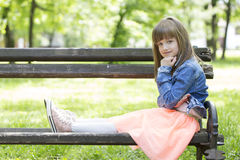 Little cute girl sitting on a bench and looking pensively. Little cute girl in a skirt sitting on a bench and looking pensively Stock Image