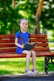 Little cute girl is sitting on a bench and is reading a book royalty free stock photos