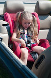 Little cute girl sitting in car seat Stock Image