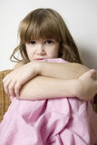 Little cute girl sitting on chair hugs her knees. Sad little cute girl sitting on chair hugs her knees Stock Photography