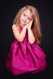 Little cute girl sitting on the floor in a pink dress Stock Photography