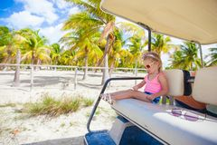 Little cute girl sitting in a golf car in a Stock Image