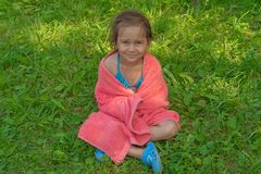 Little cute girl sitting on the grass in a pink towel after swimming in the pool and smiling stock images