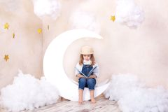 Little cute girl sitting on the moon with clouds and stars with a book in her hands and reading. The girl is learning to read. Rea