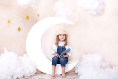 Little cute girl sitting on the moon with clouds and stars with a book in her hands and reading. The girl is learning to read. Rea stock photo