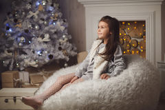 little cute girl sitting near christmas tree and fireplace Stock Photo