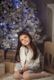 little cute girl sitting near christmas tree and fireplace Stock Photos