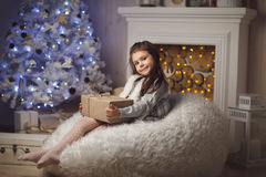 Little cute girl sitting near christmas tree and fireplace Stock Images
