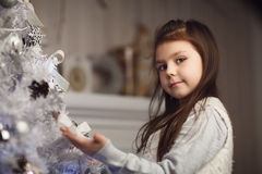 little cute girl sitting near christmas tree and fireplace Royalty Free Stock Photo