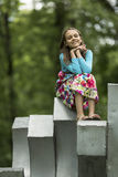 Little cute girl sitting outdoors. Happy. Stock Photography