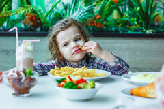 Little cute girl sitting in a restaurant and eating french fries. Stock Photo