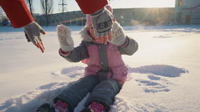 Little cute girl sitting in the snow and smiling. stock footage