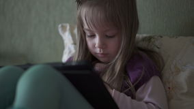 Little cute girl sitting on sofa and playing with tablet stock footage