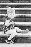 Little cute girl in sitting on the stairs Royalty Free Stock Images