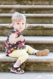 Little cute girl in sitting on the stairs with stone steps. Selective focus on face stock photo