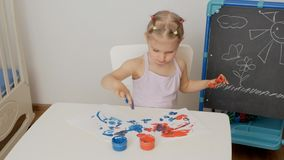 A little cute girl sitting at the table draws on paper with bright finger paints, dipping her fingers in jars of paint. A little cute girl sitting at the table stock video footage