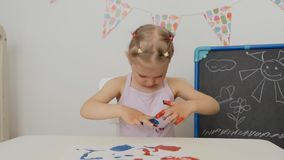A little cute girl sitting at the table draws on paper with bright finger paints, dipping her fingers in jars of paint. A little cute girl sitting at the table stock video