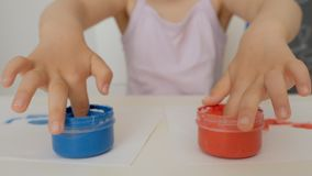 A little cute girl sitting at the table draws on paper with bright finger paints, dipping her fingers in jars of paint. A little cute girl sitting at the table stock footage