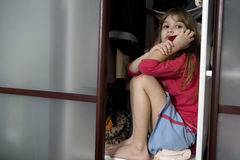 Little cute girl sitting in wardrobe Royalty Free Stock Photo