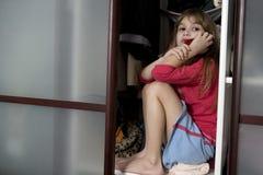 Little cute girl sitting in wardrobe Royalty Free Stock Photo