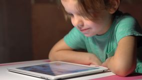 Little cute girl sitting and watching tablet. At home stock video footage