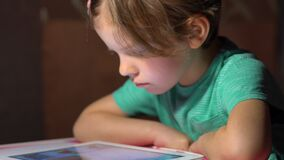 Little cute girl sitting and watching tablet. At home stock footage