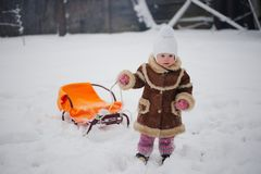 Cute girl with sled in snow Stock Image