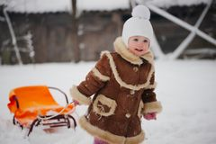 Cute girl with sled in snow Royalty Free Stock Images