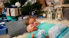 Little cute girl sleep, near the fireplace where the fire burns, hugging a doll, The child sleeps near a Christmas tree stock footage