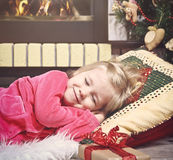 Little cute girl sleeping under the Christmas Tree waiting for S Stock Photography