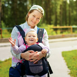 Little cute girl in sling. Mother`s hand hold her. Summer time royalty free stock photos