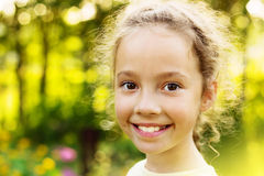 Little cute girl is smiling in the sunny summer evening. Royalty Free Stock Images