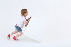 Little cute girl in sneakers pushes large white cube royalty free stock photography