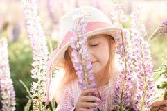 Little cute girl sniffs lupine flower at sunset. Little cute girl in straw hat sniffs lupine flower at sunset stock photos