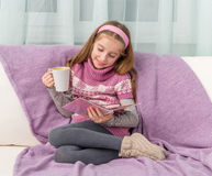 Little cute girl on sofa with cup watching a magazine Stock Photo