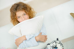 Little cute girl on sofa with pillow Stock Photo