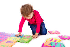 Little cute girl solving alphabet puzzle Stock Photo