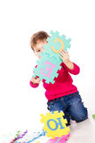 Little cute girl solving alphabet puzzle Royalty Free Stock Photo