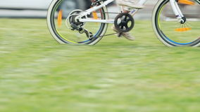 Little cute girl in sportwear riding bicycle in the city park in sunshine day. stock footage