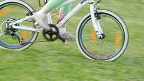 Little cute girl in sportwear riding bicycle in the city park in sunshine day. stock video