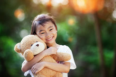Little cute girl standing in the grass holding large teddy bear Royalty Free Stock Photo