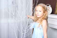 Little cute girl standing near the tree branches white. A girl in a blue dress, her white wavy hair. Studio Stock Photos